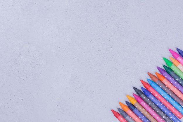 Pastelli multicolori per la lavorazione o la pittura su grigio.