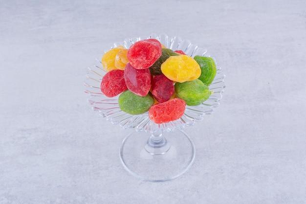 Ciliegie secche multicolori in una tazza su una superficie di cemento