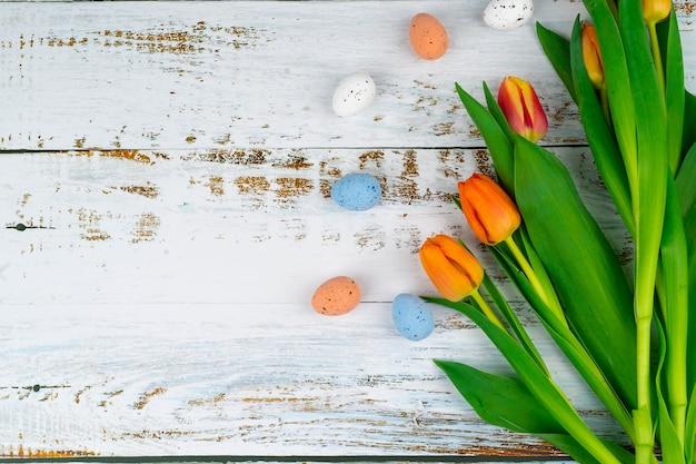 チューリップと白い木製のテーブルの上のバスケットに多色のイースター塗装斑点のある卵