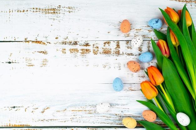 チューリップと白い木製のテーブルに多色イースター塗装斑点のある卵