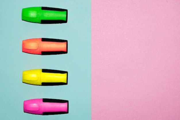 Multicolor felt tip pens on pastel pink and pastel blue background. colorful markers