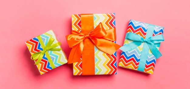 Multicolor gift boxes on pink. flat lay