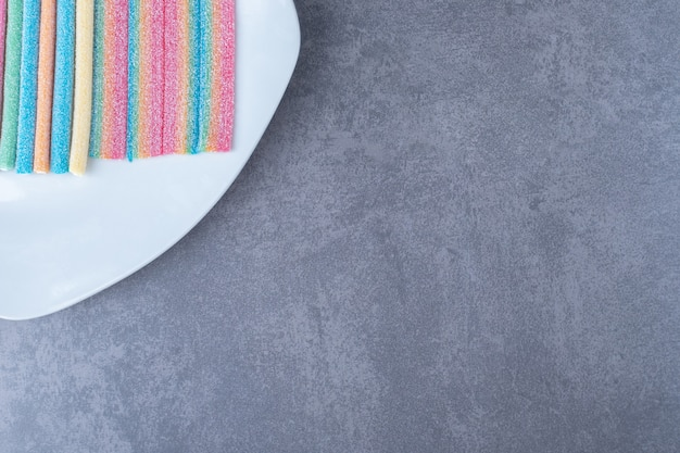 Multicolor gummy candy sweets on a plate on marble table.
