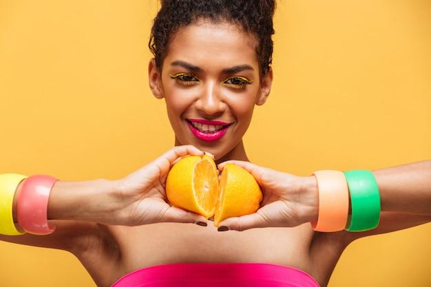 Многоцветная радостная женщина-мулатка с ярким макияжем, соединяющая две части свежего апельсина вместе, изолированная над желтой стеной
