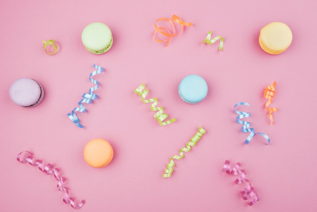 Multicolor macaroons with confetti on pink background