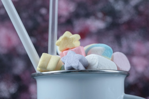 Multicolor marshmallows in a blue metallic cup.