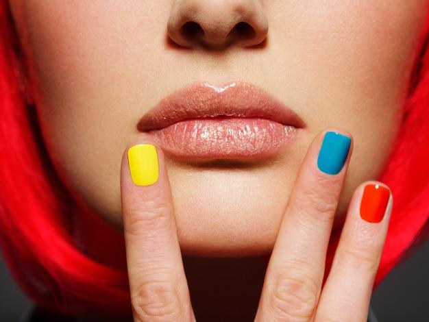 Unghie multicolori vicino alle labbra della ragazza del primo piano.