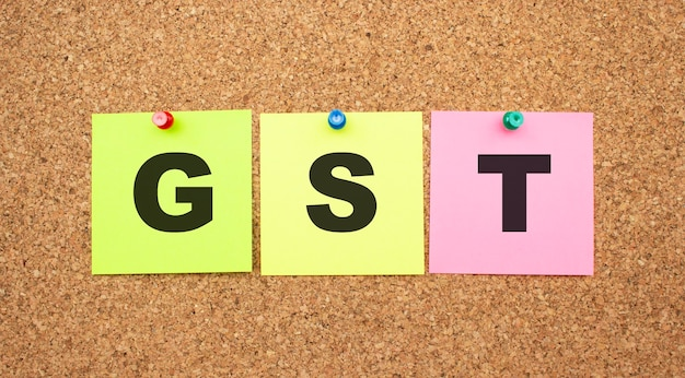 Multicolor notes with letters pinned on a cork board. word gst. work space.