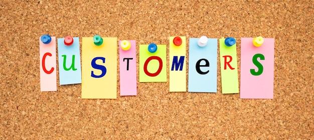 코르크 판에 고정 된 글자가있는 여러 가지 빛깔의 노트 word customers