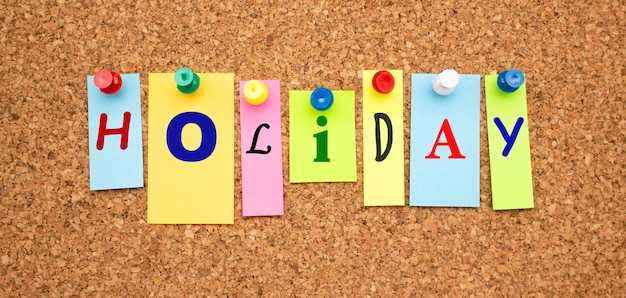 코르크 판에 고정 된 글자가있는 여러 가지 빛깔의 노트 word holiday
