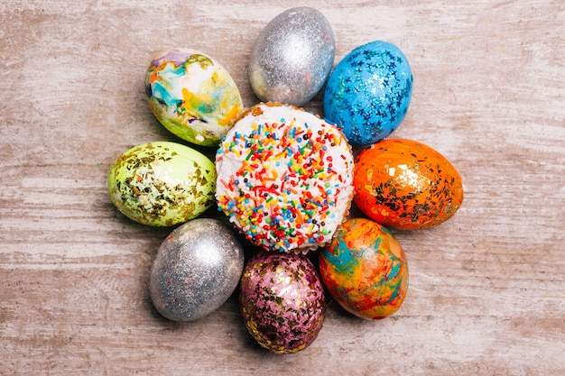 色とりどりのペイントされたイースターエッグと木製の背景に振りかけるケーキクリーチ。創造的な休日のお祝いの装飾