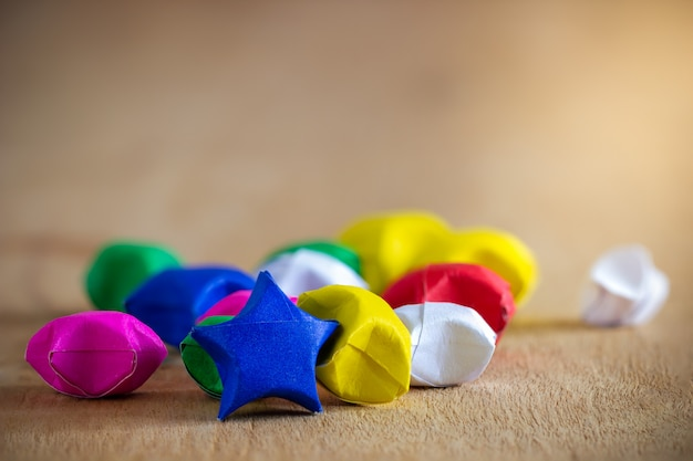 Multicolor paper star laid on wooden table with morning sunlight.