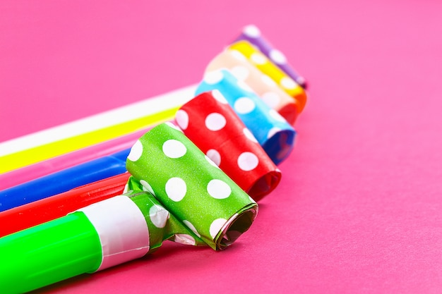 Multicolor party blowers on pink background