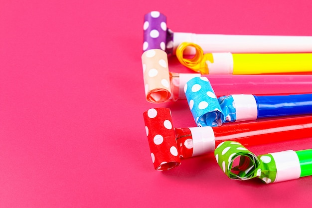 Multicolor party blowers on pink color. multicolored party whistles. decor for a birthday.