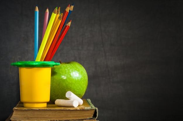 黒板学校の概念に対して古い本に多色鉛筆チョークと青リンゴ