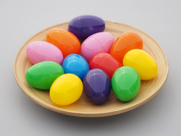 Multicolor plastic easter eggs in a plate on gray.