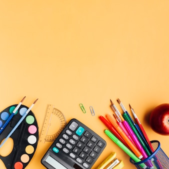 Multicolor school supplies and red apple scattered on yellow desk