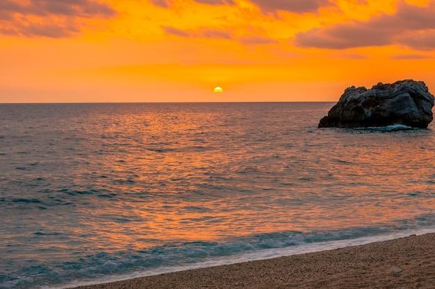 穏やかな水の上に多色の日の出。地中海のギリシャの海岸の砂浜のストリップ