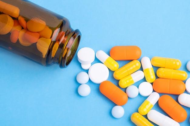 青いテーブルの上のガラス瓶からの多色錠剤とピルカプセルのクローズアップ-画像