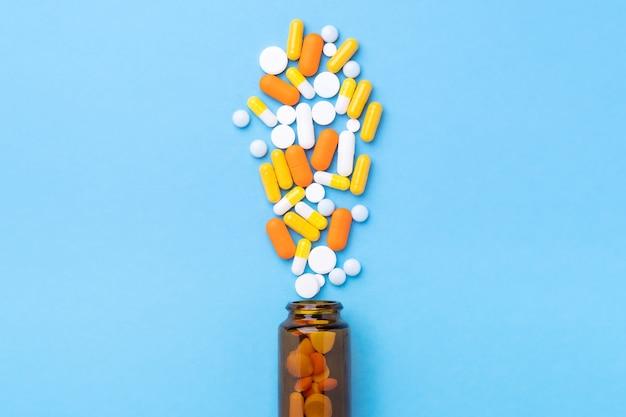 青いテーブルの上のガラス瓶からの多色錠剤とピルカプセル上面図-画像
