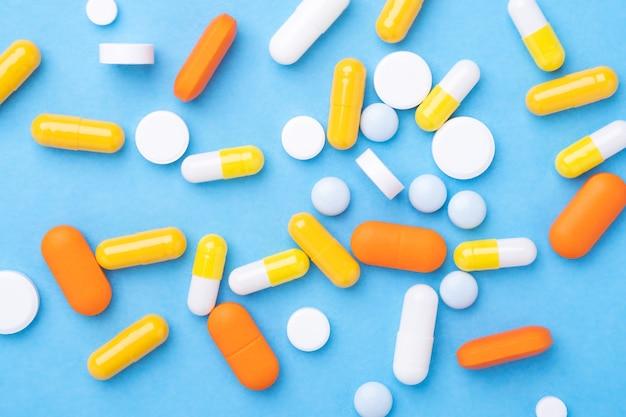 青いテーブルの上の多色錠剤と丸薬カプセルクローズアップ上面図-画像