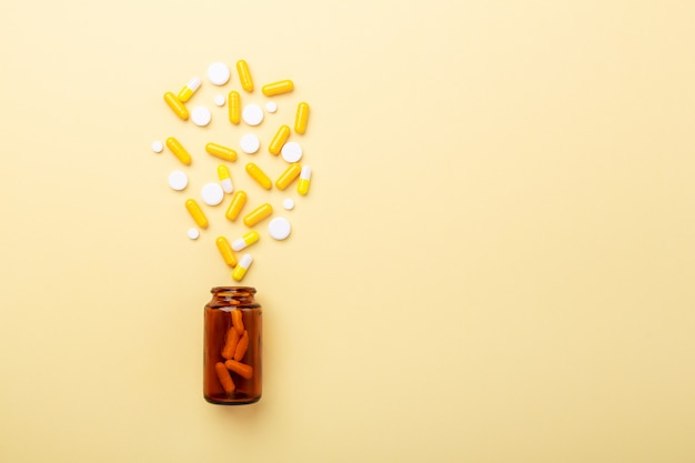 Multicolor tablets and pills capsules from glass bottle on yellow