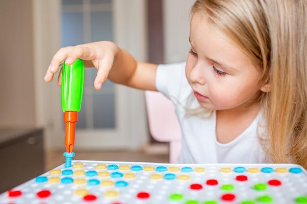 Маленькая белокурая девушка сидя на таблице дома играя с отверткой игрушки и multicolor винтами. раннее образование.