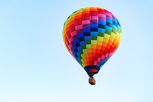 Multicolored air balloon in clear blue sky close up