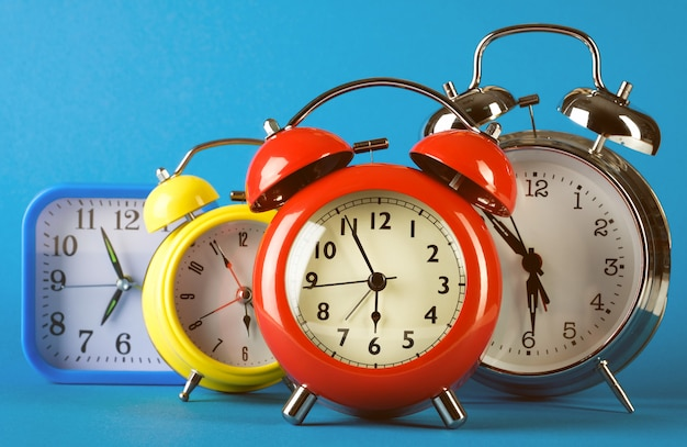 Multicolored alarm clocks in retro vintage style on a bright blue background.