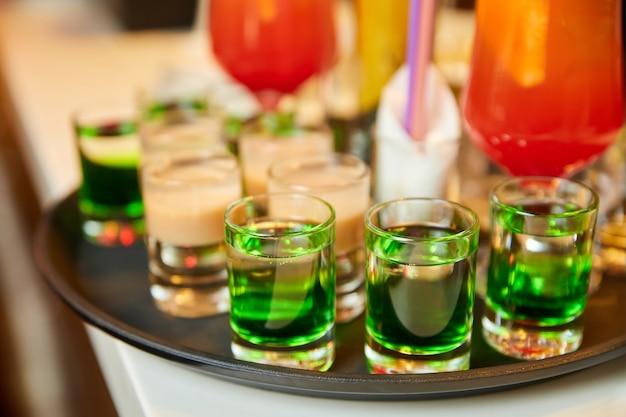 얼음과 빨대가 있는 여러 가지 빛깔의 알코올 및 무알코올 칵테일