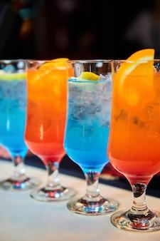 여러 가지 빛깔의 알코올 및 무알코올 칵테일과 얼음.