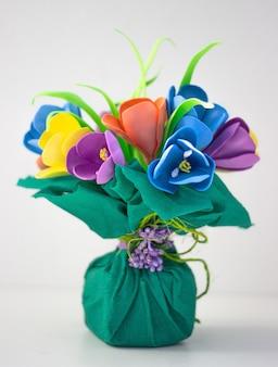 Разноцветные искусственные изолированные цветы на светлой однотонной поверхности