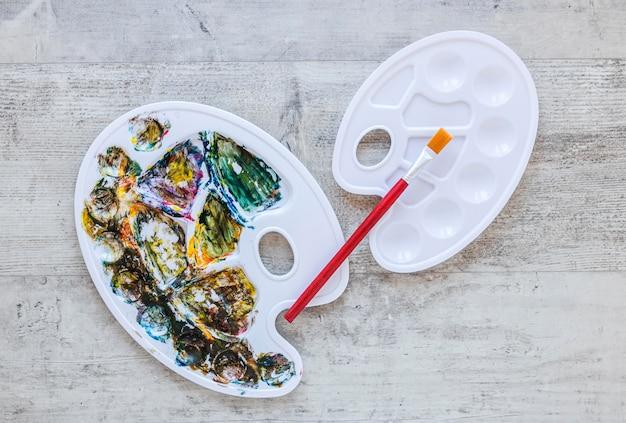 Разноцветная палитра и кисть подноса художника