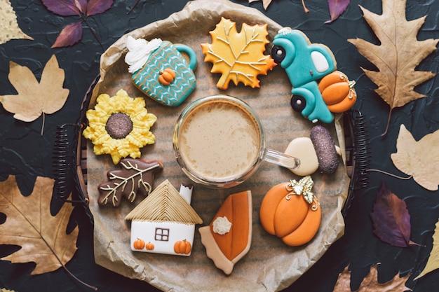 Разноцветное осеннее печенье с кофе на черном фоне. осенняя концепция.