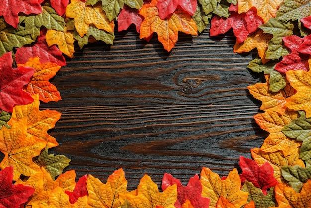色とりどりの秋のカエデの葉は、木製の背景に。テキストの場所