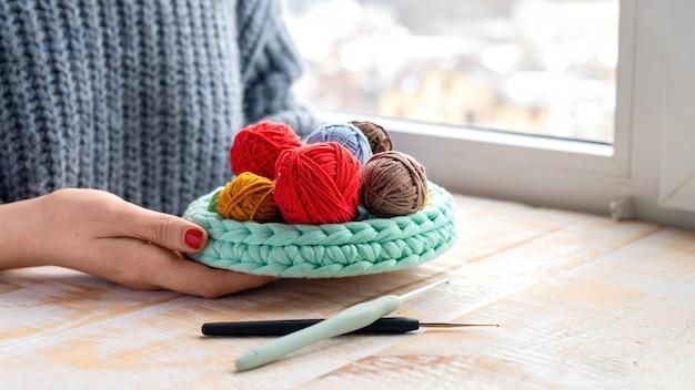 ニットのソファの中や近くにある色とりどりの毛糸のボール