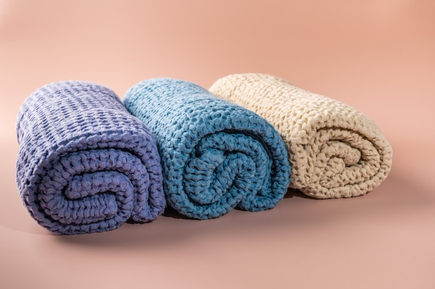 Multicolored bath and spa towels twisted into a roll on pink