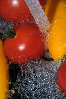 色とりどりのピーマンと赤熟したトマトは、黒い背景のきれいな水のクローズアップマクロ写真で洗われます
