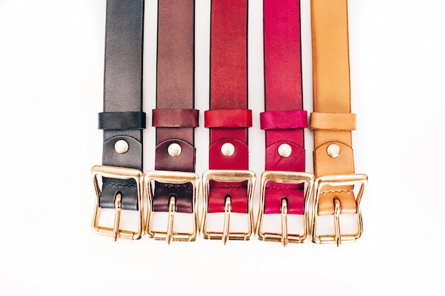 Multicolored belts. a lot of leather belts on a white background. red, yellow, blue, brown, green belts are carved on a white