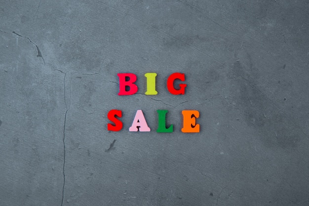 The multicolored big sale word is made of wooden letters on a grey plastered wall.