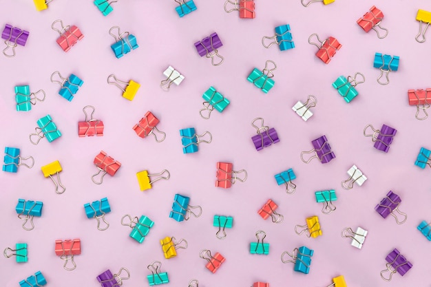 Multicolored binder clips scattered over a pink background