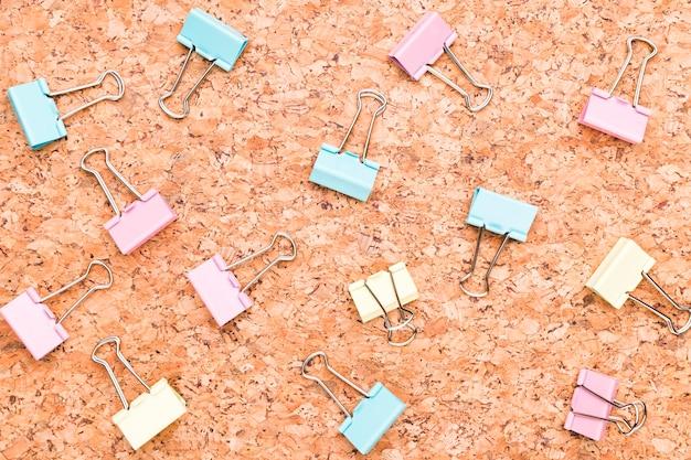 Multicolored binder clips on wooden desk