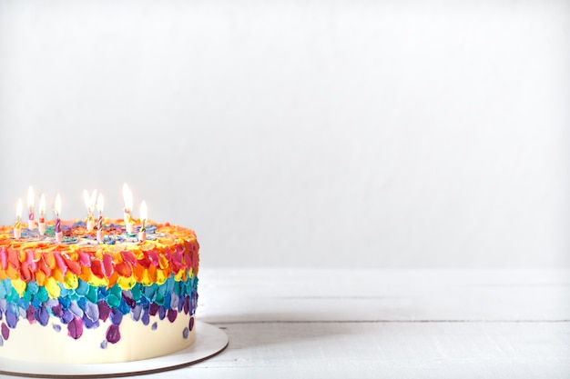 A multicolored birthday cake decorated with burning candles. happy birthday greetings concept.