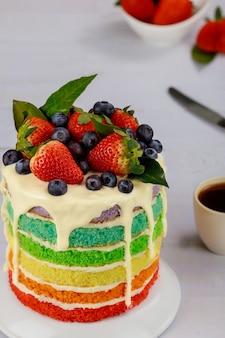 新鮮なベリーと一杯のコーヒーで飾られた色とりどりのバースデーケーキ。