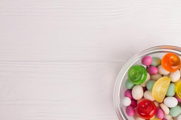 ガラスのボウルに色とりどりのボンボンスイーツ。白い木製のテーブルの上のカラフルなキャンディー。上面図