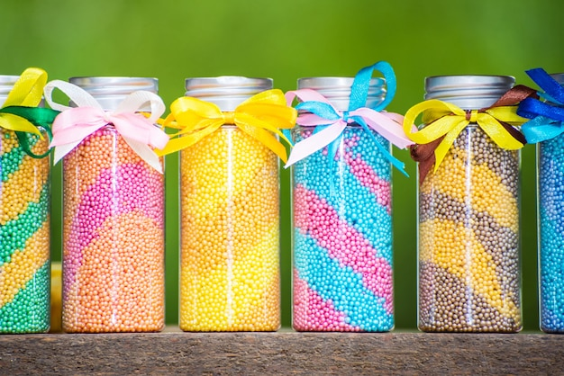 Multicolored bottles with foam for a bath with bows on a green background