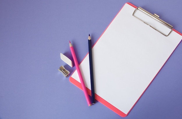Multicolored, bright, colorful pencils are located at the bottom at an angle and a notebook for your text on a violet background.