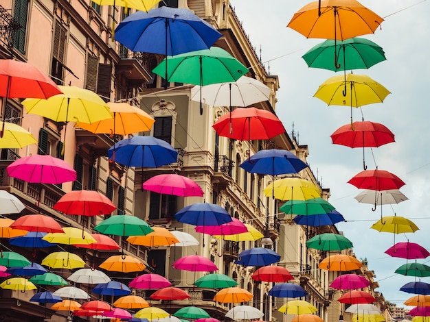 Multicolored and bright umbrellas hanging between houses