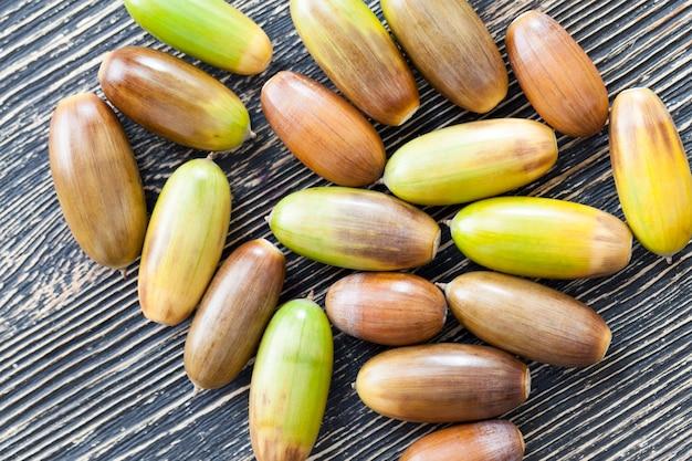 色とりどりの茶色と緑のオークナッツ-木製のテーブルのどんぐり、秋の時間