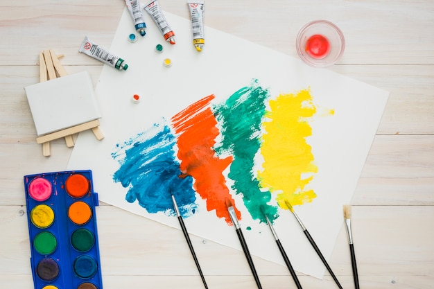 Multicolored brushstroke on white page with painting equipment on wooden table